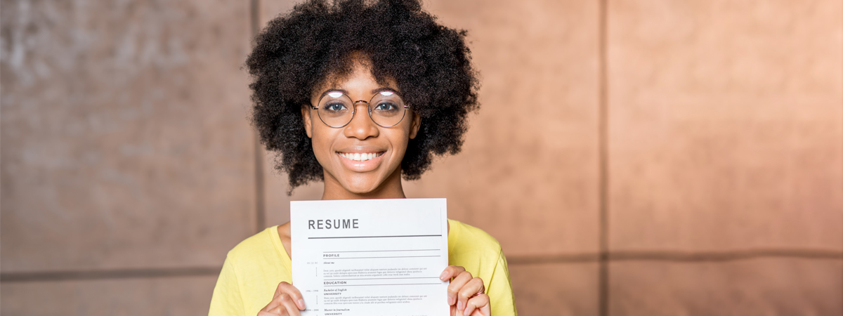 Woman in yellow shirt holding resume