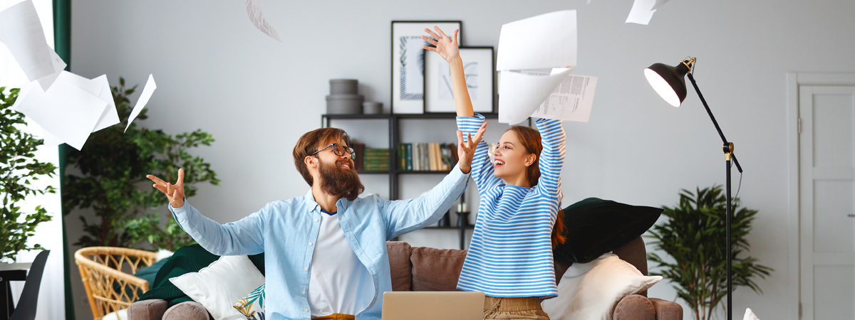 A man and a woman in living room with papers flying all around them