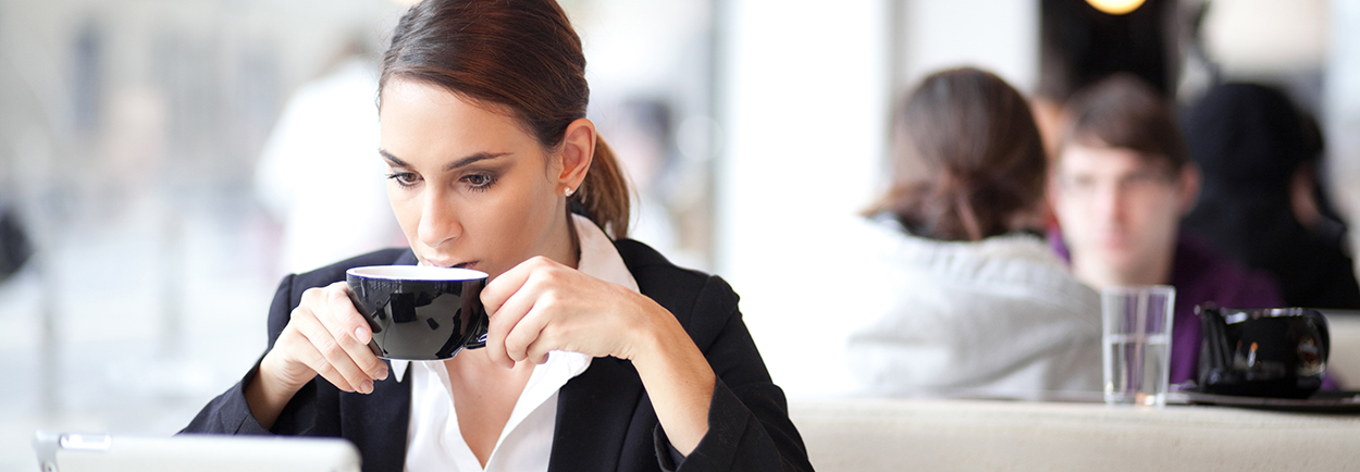 Businesswoman drinking coffee on laptop