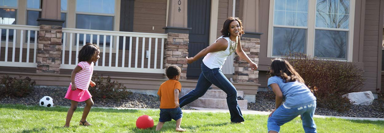 Mortgage home loan buyer playing outside family home with children