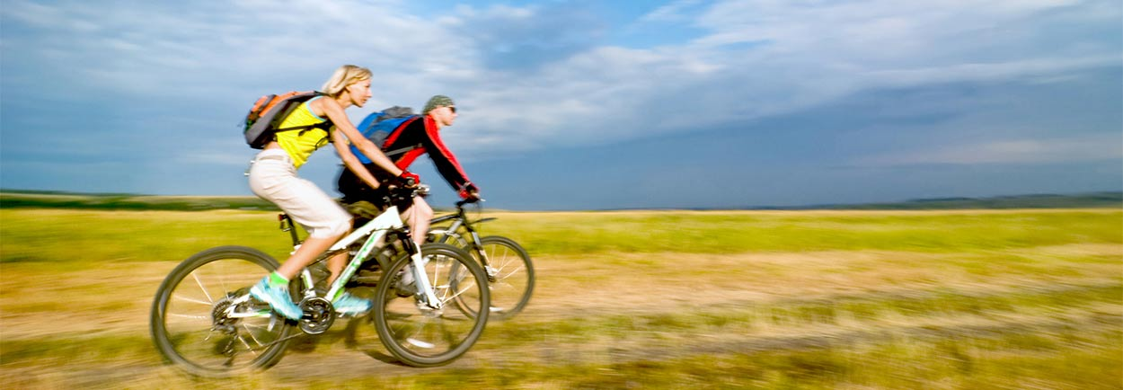 Couple riding bikes in open field
