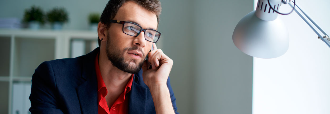 Man in glasses on cell phone in office