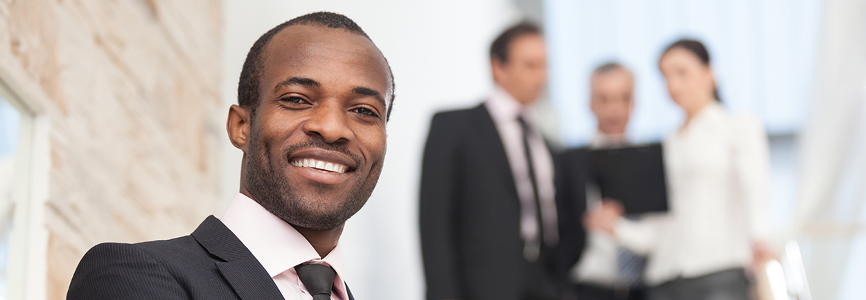 Focus on Businessman smiling at camera with others in background