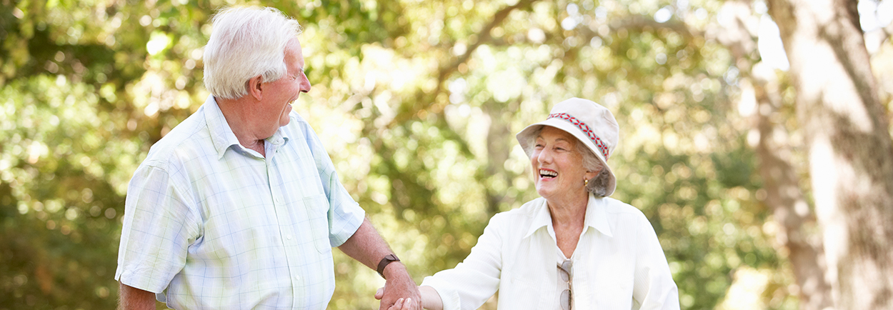 Elderly couple outside holding hands