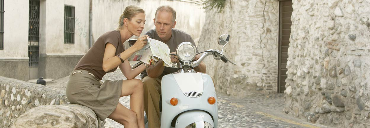 Couple traveling on motorcycle looking at map